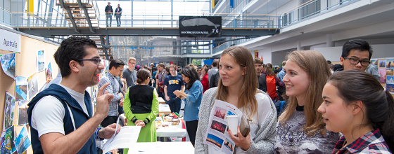 International Day 2016: Students talking to each other at a booth.